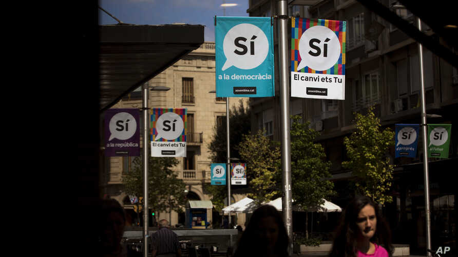 """Banners urging support for a """"yes"""" vote in a Catalan independence referendum hang on poles as people walk along a street in Sabadell, near Barcelona, Spain, Sept. 7, 2017."""