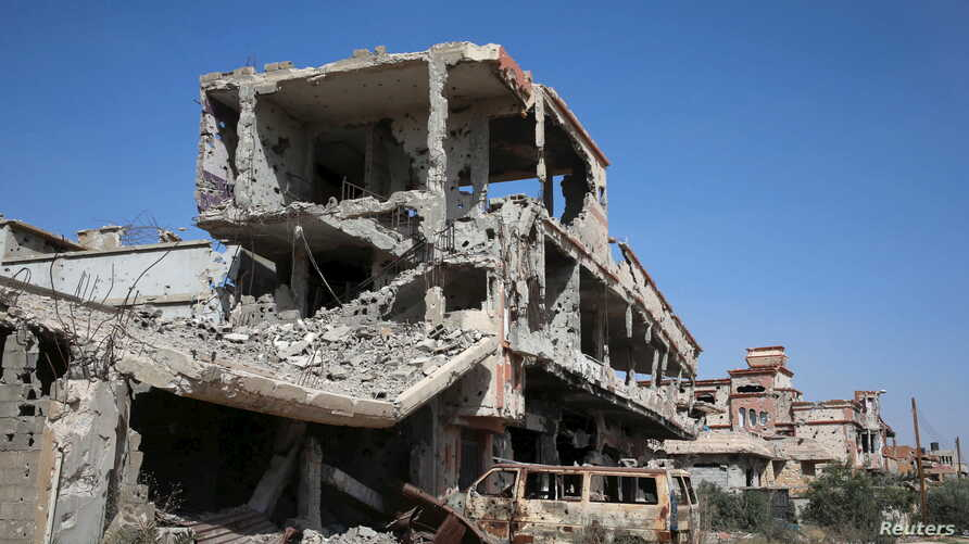 FILE - Buildings damaged during clashes between troops loyal to Libya's eastern government and the Shura Council of Libyan Revolutionaries, an alliance of former anti-Gaddafi rebels, are seen during a cleanup of the debris by pro-government people in