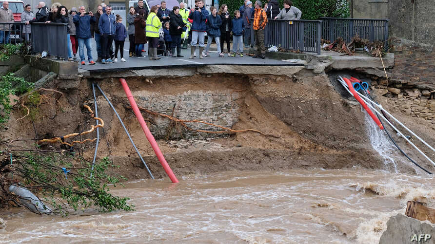 People stand in front of a collapsed road on Oct. 15, 2018 in Villegailhenc in the Aude department after it was particularly badly hit by heavy rain storms which swamped parts of southwestern France, flooding rivers and cutting roads, killing at leas