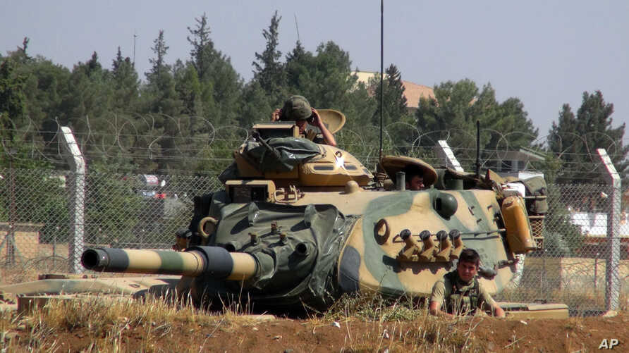 FILE - A Turkish army tank appears near the Syrian border in Suruc, Turkey, Sept. 3, 2016. Since then, tanks have entered Syria's Cobanbey district, northeast of Aleppo, as part of the Euphrates Shield operation to support Syrian rebels against the I...
