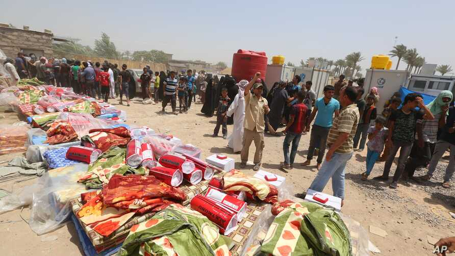 Displaced civilians from Ramadi wait to receive humanitarian aid from the United Nations in a camp in the town of Amiriyat al-Fallujah, west of Baghdad, Iraq, Friday, May 22, 2015. The United Nations World Food Program said it is rushing food assista
