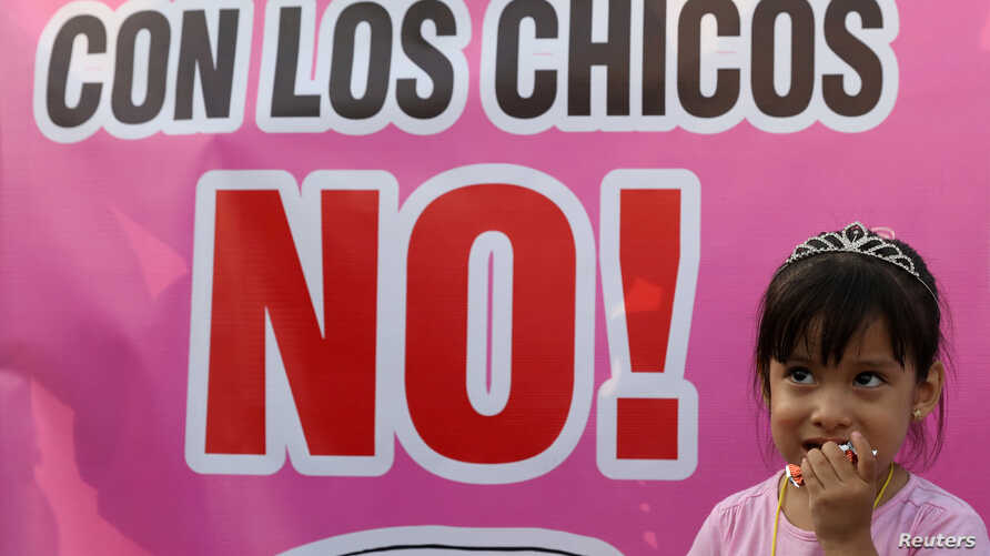 A child stands next to a sigh reading: 'No with the children' during a protest against child abuse and violence in Lima, Peru, Feb. 8, 2018.