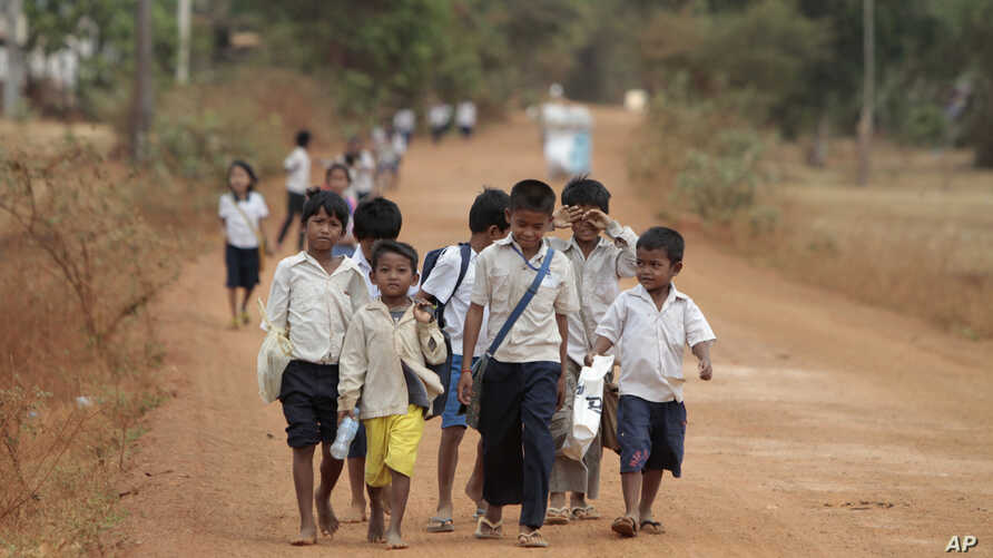 FILE - Cambodian school children walk home after a morning school session at Tnoat Kpoh village in the outskirts of Phnom Penh, Cambodia.
