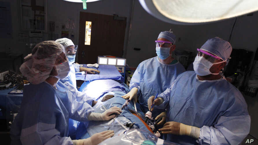 Dr. Keith Melancon, right, Georgetown's kidney transplant director, performs the surgery to harvest the kidney from donor Tom Otten, at Georgetown University Hospital in Washington.