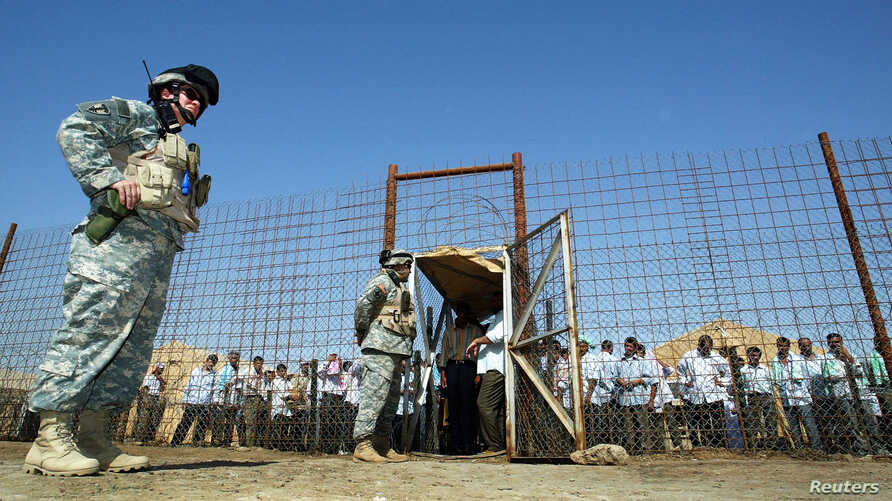 FILE - U.S soldiers stand guard as Iraqi prisoners wait to be released at Abu Ghraib prison, west of Baghdad, June 23, 2006.