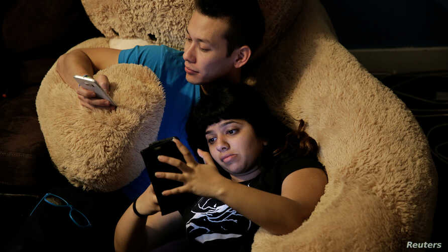 Cory Brandi (L), 25, and Isha Padhye (right), 23, who is a UI engineer, check their phones as they rest together on large stuffed bear at The Negev tech house in San Francisco, California, Feb. 4,  2017.