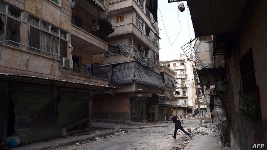 A Syrian rebel fighter runst to avoid snipers of government forces in the Saladin district of Aleppo, April 8, 2013.