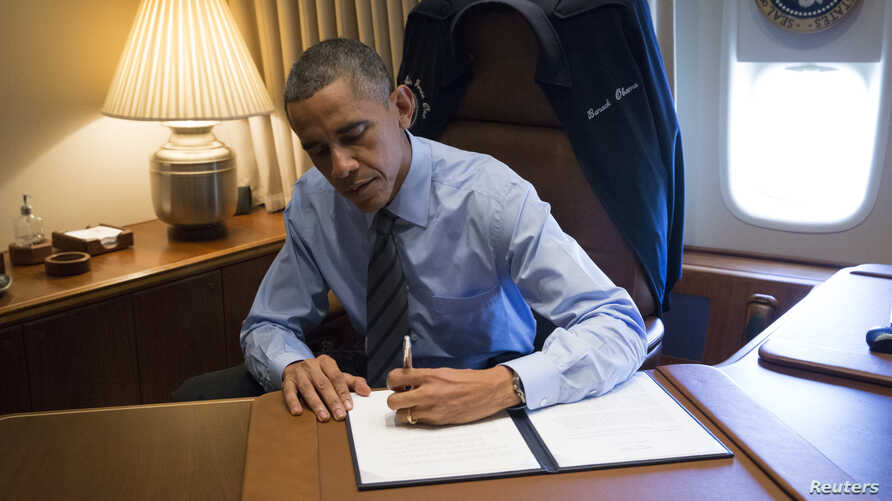 President Barack Obama signs two presidential memoranda associated with executive actions on immigration from his office on Air Force One upon his arrival in Las Vegas, Nevada, Nov. 21, 2014.