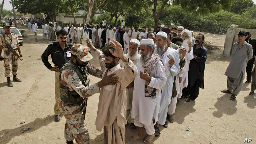 A Pakistani paramilitary soldier checks voters before they enter a polling station to cast their ballots, in Karachi, Pakistan, May 11, 2013.