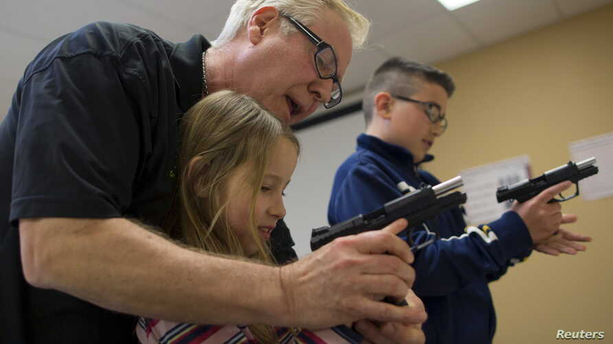 Instructor Jerry Kau shows student Joanna Zuber how to load a magazine into a handgun alongside Sam Minnifield during a Youth Handgun Safety Class at GAT Guns in East Dundee, Illinois, April 21, 2015.