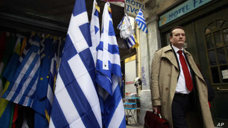 A man walks next to a kiosk selling Greek flags in Athens, February 21, 2012, the same day eurozone finance ministers approved a $172 billion bailout deal to help the debt-laden country avert default.