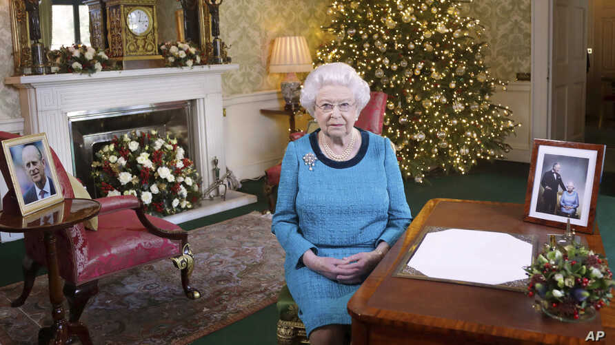 In this photo released Dec. 25, 2016, Britain's Queen Elizabeth II poses for a photo, sitting at a desk in the Regency Room of Buckingham Palace in London, after recording her traditional Christmas Day broadcast to the Commonwealth.
