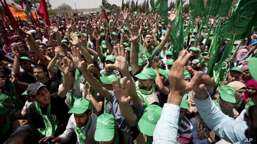 FILE - Palestinian students and supporters of the Hamas movement chant slogans during a rally near the West Bank city of Ramallah, April 26, 2016.