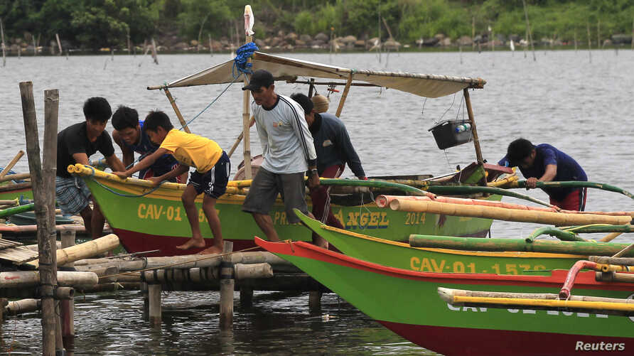 Residents secures their small boat in a safer area in preparations for the strong winds brought by Typhoon Rammasun, locally name Glenda, in a coastal area of Cavite city, south of Manila, July 15, 2014.