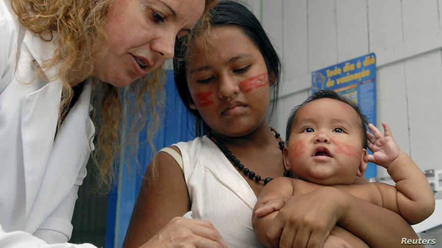 FILE - A health worker vaccinates a boy from the Cambeba tribe against the flu in the center of Brazil's Amazon Basin along the Cueira River.