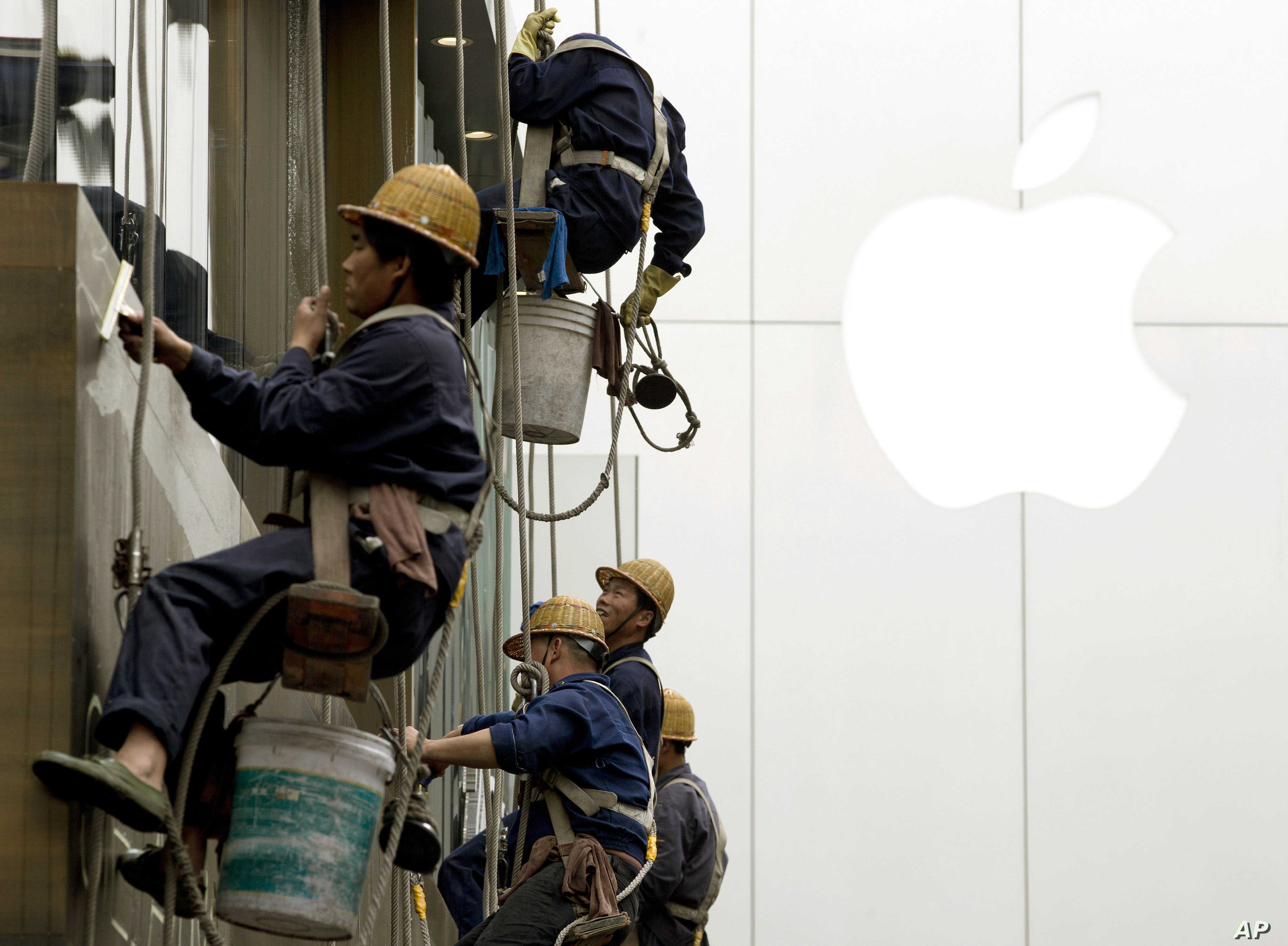 Workers clean windows near Apple's retail store in Beijing. China reported an unexpected contraction in exports in March, raising the danger of job losses as Beijing tries to overhaul its slowing economy, April 10, 2014.