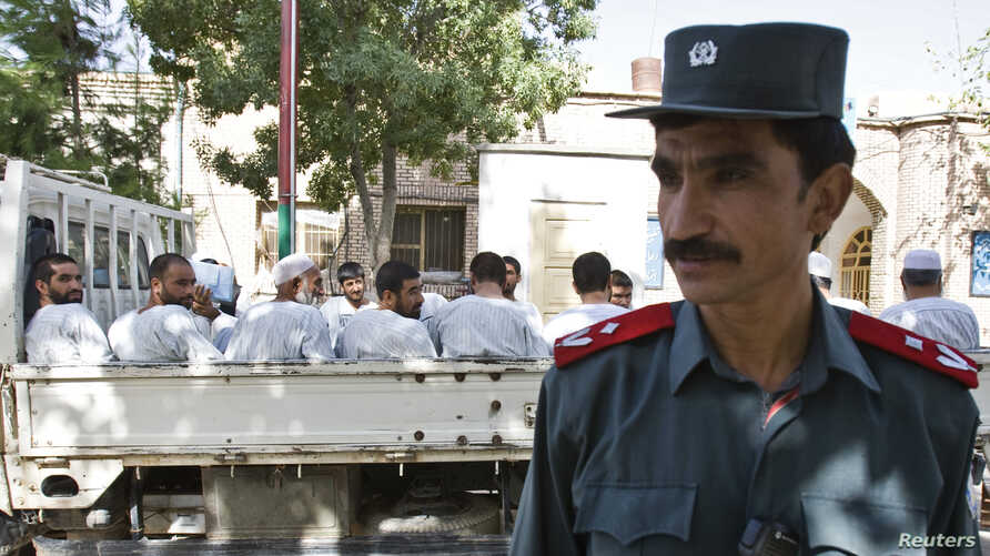 An Afghan police officer stands guard in front of a truck carrying Afghan prisoners on their way to court in Herat, western Afghanistan August 16, 2009