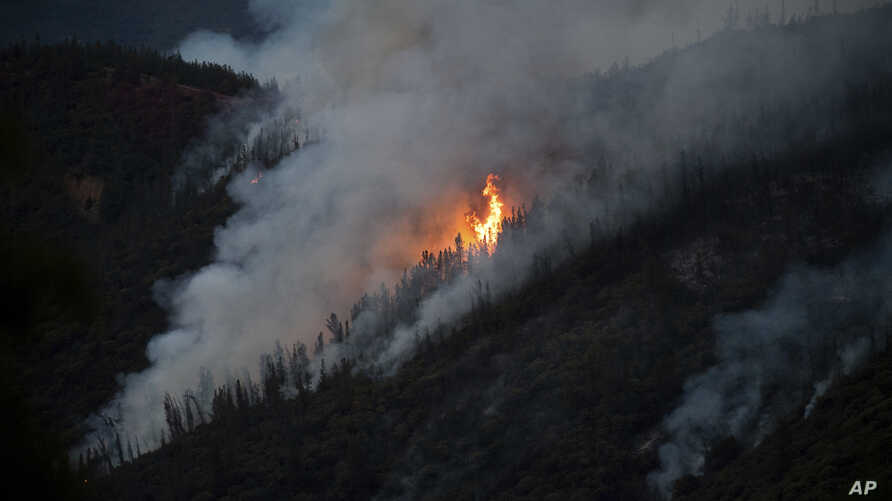 Flames from the Ferguson Fire burn down a hillside in unincorporated Mariposa County Calif., near Yosemite National Park, July 15, 2018.