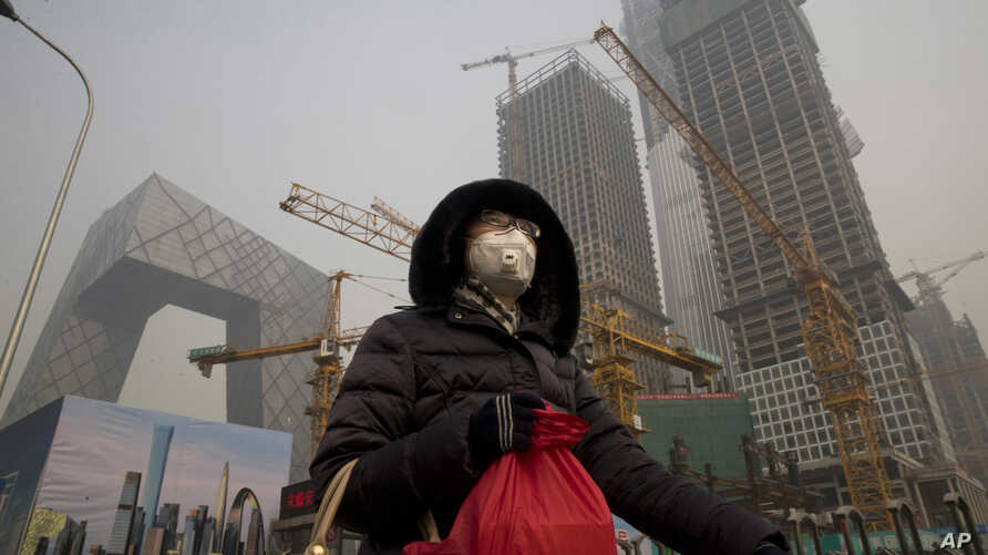 A woman wears a mask as she walks past a construction site as smog continues to choke Beijing, China, Jan. 6, 2017.