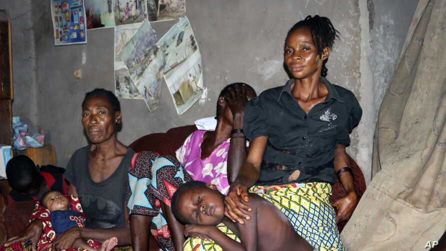 Family and friends comfort Irene Mboyo Mola, 30, whose husband died in May from Ebola and whose six children have been vaccinated but she refused, saying she doesn't believe he died from the disease, in her house in the town of Mbandaka, Congo, June
