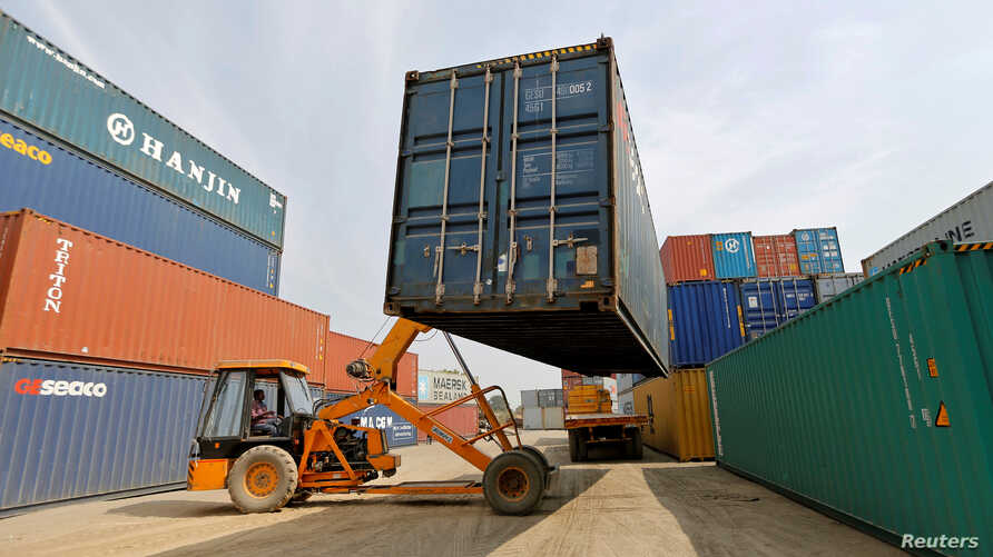 FILE - A mobile crane carries a container at Thar Dry Port in Sanand in the western state of Gujarat, India, Feb. 13, 2017.