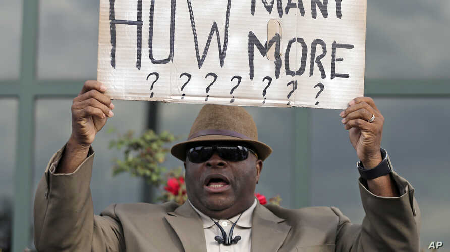 Rev. Arthur Prioleau holds a sign during a protest in the shooting death of Walter Scott at city hall in North Charleston, S.C., Wednesday, April 8, 2015.  Scott was killed by a North Charleston police officer after a traffic stop on Saturday. The of