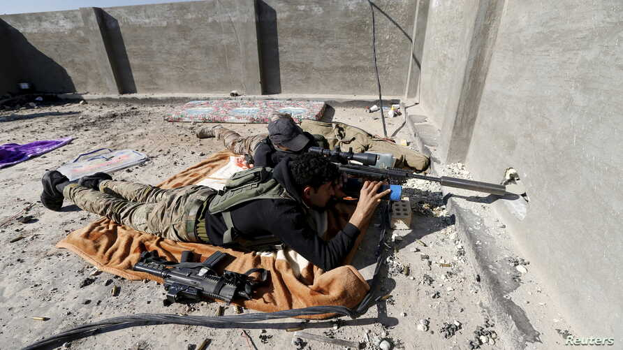 Iraqi security forces sniper looks through rifle scope while guarding position in the city of Ramadi, Jan. 16, 2016.