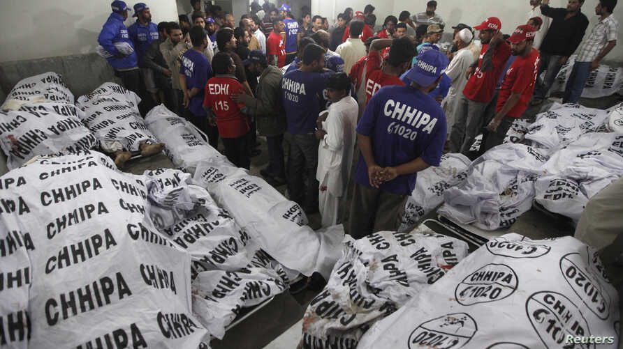 Rescue workers and residents gather to identify relatives at a morgue after a bomb blast in a residential area in Karachi March 3, 2013.