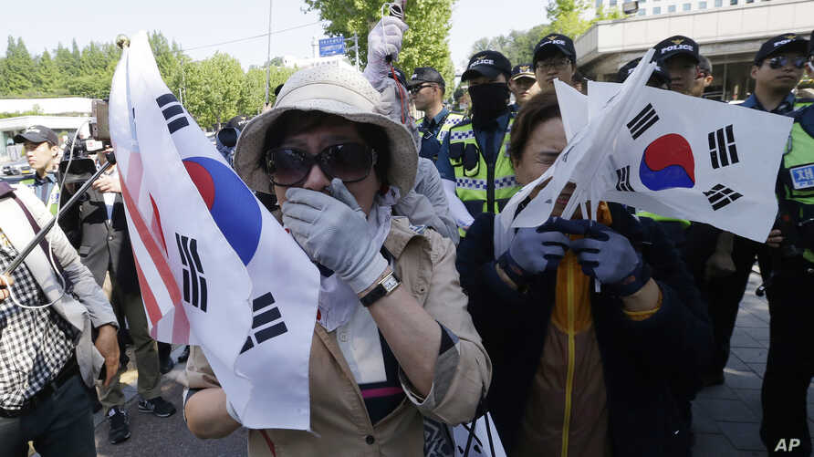 Supporters of former South Korean President Park Geun-hye weep to demand her release as a bus carrying her arrives at the Seoul Central District Court in Seoul, South Korea, May 25, 2017.