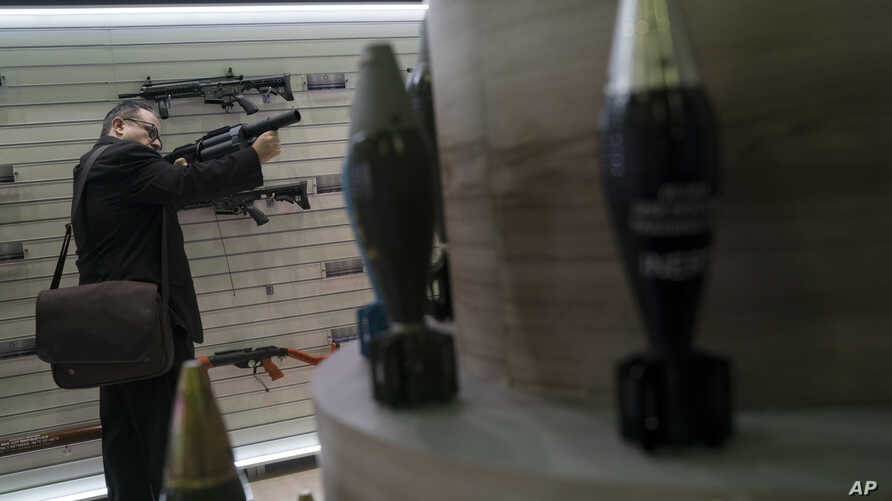A man tries a multi shot riot gun displayed at the LAAD Defense and Security International Exhibition in Rio de Janeiro, Brazil, April 2, 2019.