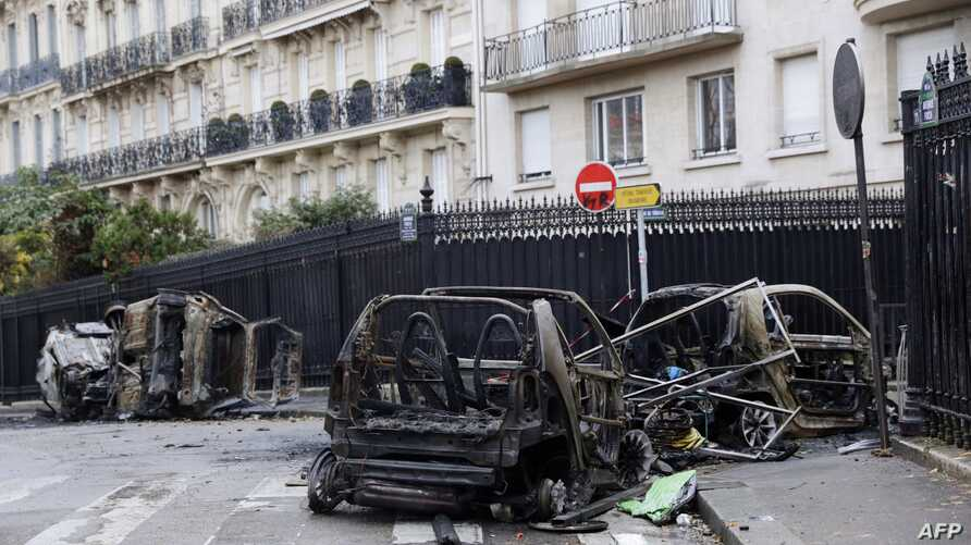 Burned cars sit in a street of Paris, Dec. 2, 2018, a day after clashes during a protest of yellow vests (gilets jaunes) against rising oil prices and living costs. Anti-government protesters torched dozens of cars and set fire to storefronts during ...