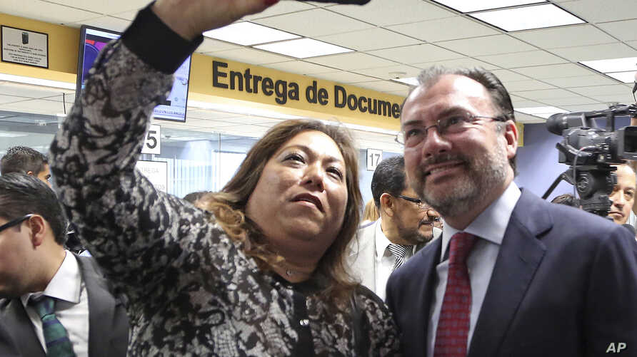 Elisa Jimenez, director of the California Mental Health Connection, takes a selfie with Mexico's Secretary of Foreign Relations Luis Videgaray at the dedication of a mental health facility at the Consulate General of Mexico in Los Angeles, Sept. 12,