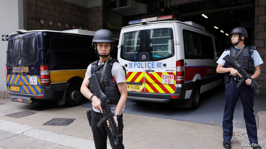 Armed policemen stand guard at the entrance as a prison car carrying former British banker Rurik Jutting enters High Court to launch his appeal, in Hong Kong, Dec. 12, 2017.