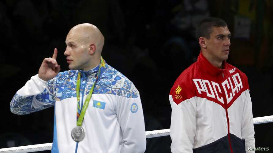 Silver medalist Vassiliy Levit of Kazakhstan reacts to the audience as gold medalist Evgeny Tishchenko of Russia stands at attention for the singing of the national anthem at the 2016 Olympics in Rio de Janeiro, Aug. 15, 2016.