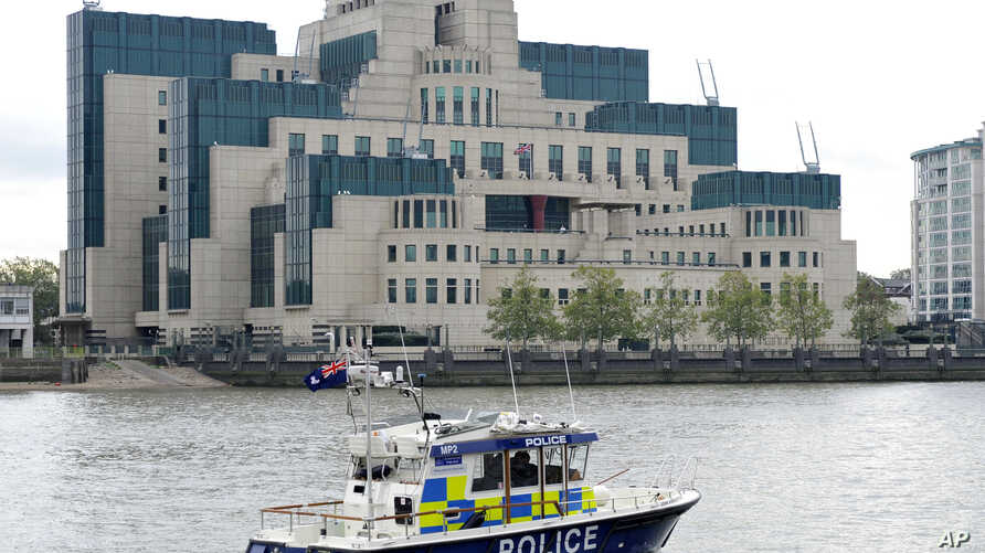 FILE - A police boat patrols on the River Thames near the building of British Secret Intelligence Service, SIS, also known as MI6, in London.
