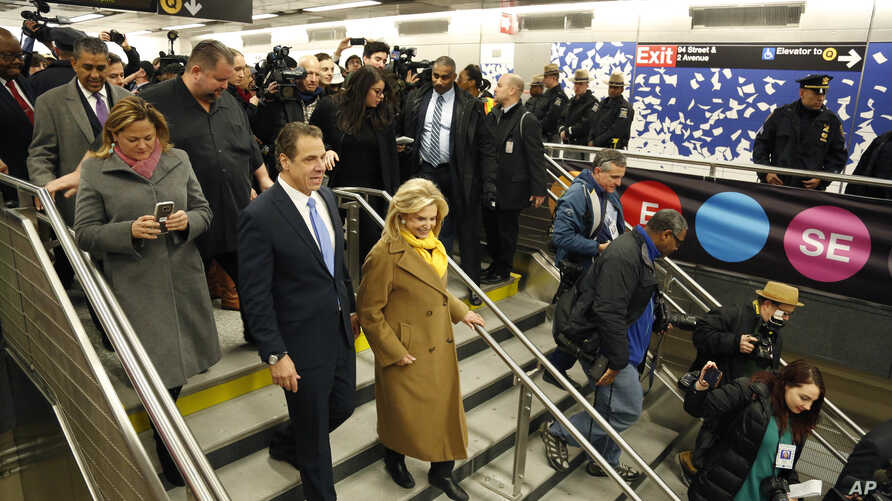 New York Gov. Andrew Cuomo (left) is surrounded by other guests and reporters as he tours the new 86th Street subway station in New York, Dec. 22, 2016. The first phase of the Second Avenue subway line, which has three stops, is scheduled to open Jan