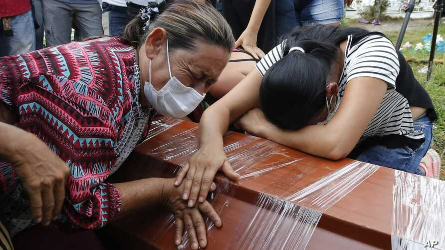 Women cry over the coffin of a relative, a victim of a deadly avalanche due to heavy rains, during a mass burial in Mocoa, Colombia, April 3, 2017.