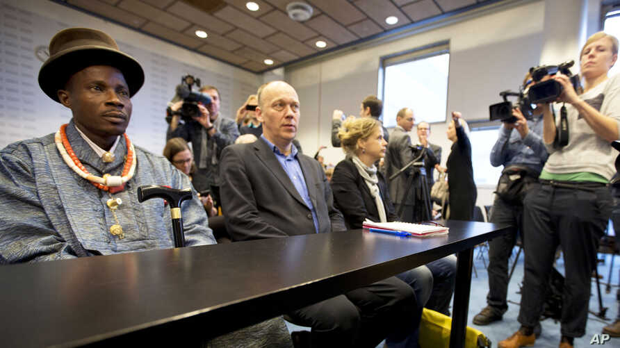 Friends of the Earth campaign leader Geert Ritsema (2 L), and plaintiff Eric Dooh (L) wait for the start of the ruling in the court case of Nigerian farmers against Shell, in The Hague, Netherlands, January 30, 2013.