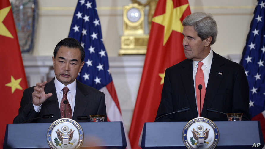 Secretary of State John Kerry, right, listens as Chinese Foreign Minster Wang Yi, left, speaks before their bilateral meeting at the State Department in Washington, Sept. 19, 2013.