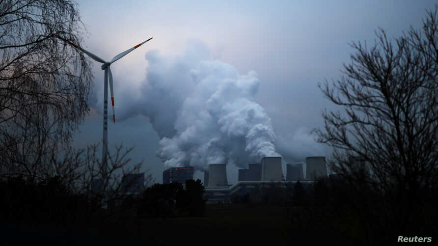 FILE - Water vapor rises from the cooling towers of the Jaenschwalde lignite-fired power plant of Lausitz Energie Bergbau AG beside a wind turbine in Jaenschwalde, Germany, Jan. 24, 2019.