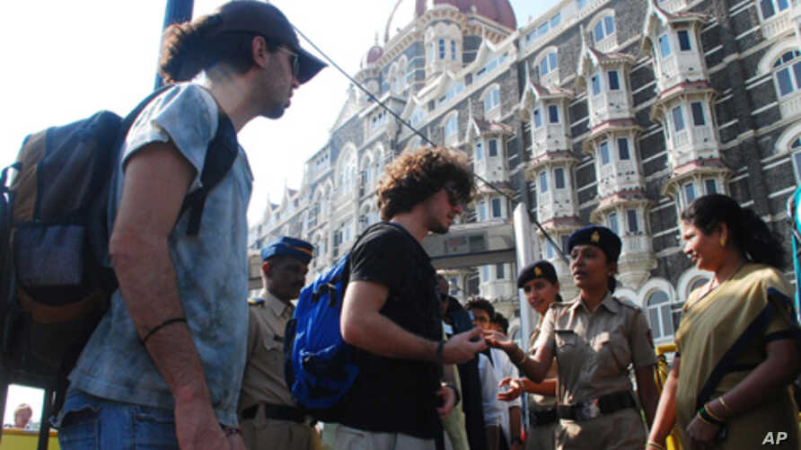 Police stop foreign tourists to check their belongings at a security checkpoint outside the Taj Mahal Palace hotel in Mumbai  24 Dec, 2010. Police have launched a manhunt for four men they said belonged to a Pakistan-based militant group and had ente