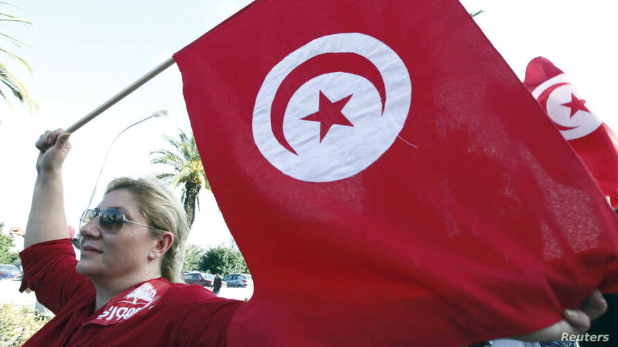 A woman waves a Tunisia flag during a rally to protest against religious and political violence in Tunis, Oct. 22, 2012.