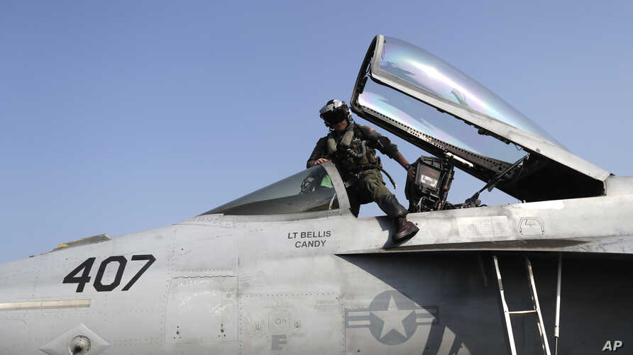FILE - A U.S. fighter pilot gets into the cockpit of a Super Hornet jet before launching from the deck of the U.S.S. Dwight D. Eisenhower aircraft carrier towards targets in Iraq and Syria. Nov. 22, 2016. A Super Hornet reportedly downed a Syrian SU-