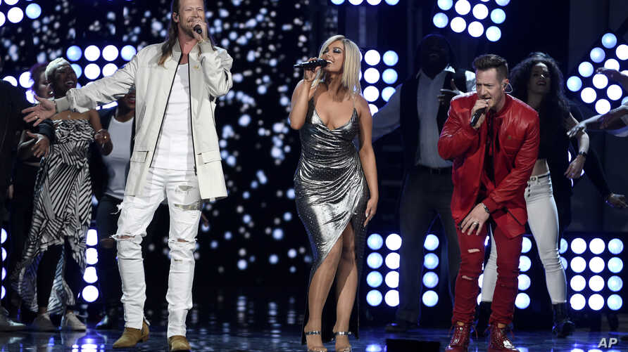 """FILE - Tyler Hubbard, right, and Brian Kelley, left, of Florida Georgia Line, and Bebe Rexha, center, perform """"Meant to Be"""" at the 53rd annual Academy of Country Music Awards in Las Vegas, April 15, 2018."""
