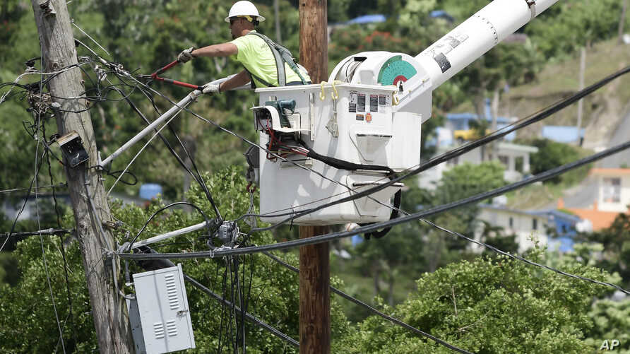 FILE - A worker from the Cobra Energy Company, contracted by the Army Corps of Engineers, installs power lines in the Barrio Martorel area of Yabucoa, Puerto Rico, May 16, 2018.