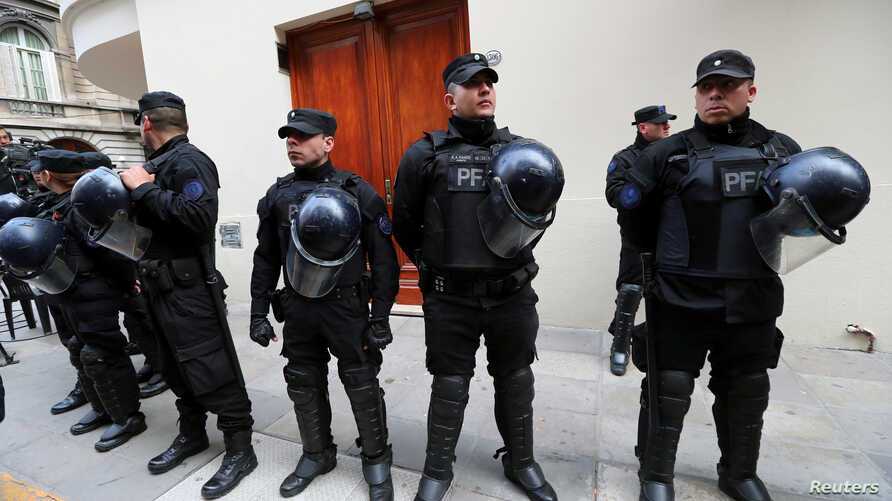 Policemen stand outside the entrance of former Argentine President and senator Cristina Fernandez de Kirchner's home during a raid ordered by a judge in Buenos Aires, Argentina, Aug. 23, 2018.
