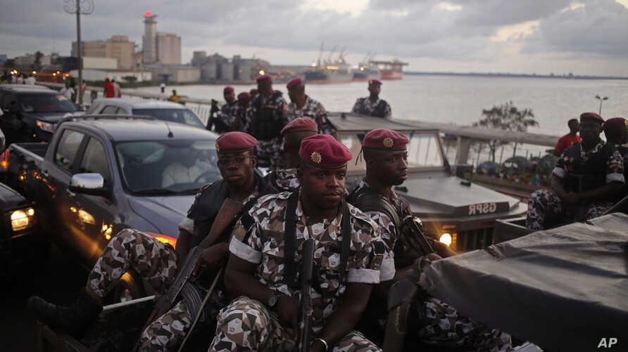 FILE - Ivory Coast troops provide security during an election rally of Ivory Coast incumbent President Alassane Ouattara in Abidjan, Ivory Coast.  Some unidentified soldiers launched mutinies in three cities across this West African country Jan. 6, 2