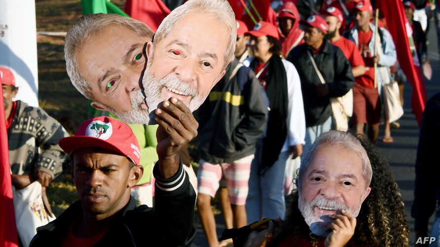 "Members of the Landless Movement, holding masks of former Brazilian President Luiz Inacio Lula da Silva, take part in the ""Free Lula"" march near Brasilia, Aug. 14, 2018."