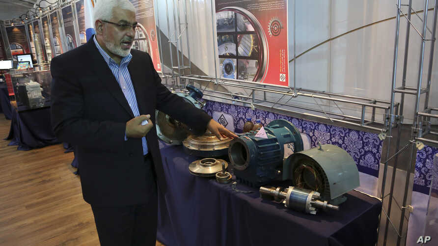 Deputy head of the Atomic Energy Organization of Iran Asghar Zarean explains about a part of a machine of the country's nuclear facilities in Tehran, Iran, Sept. 1, 2014.