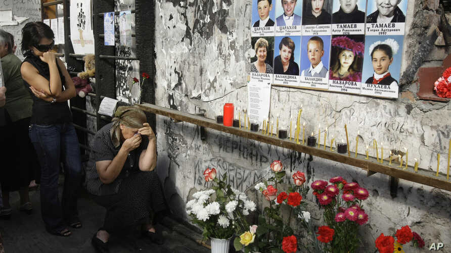 FILE - Women react in the gym of the ruined school, scene of the hostage crisis, in Beslan, Russia, Sept. 1, 2009.